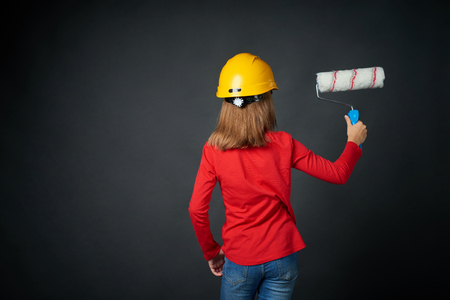 Decoration, renovation and reconstruction concept. Back view of a girl painting black wall with a paint roller brush