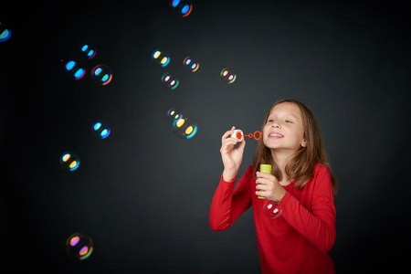 Lovely pretten girl blowing soap bubbles in studio over black background 스톡 콘텐츠