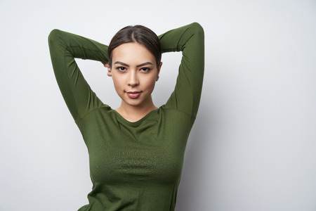 Happy smiling brunette female in green shirt standing with hands over head