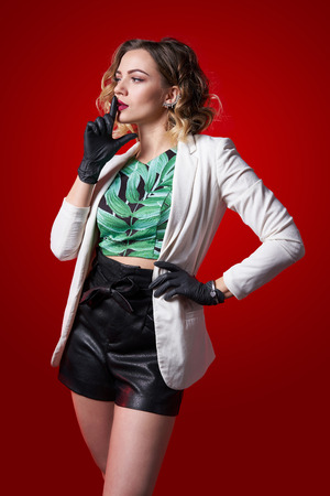 Beautiful fashionable female wearing rubber gloves looking to side and gesturing finger on lips, on red background