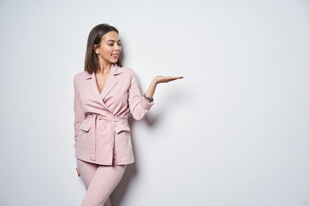 Smiling brunette woman wearing pink suit standing by white wall holding copy space on the palm