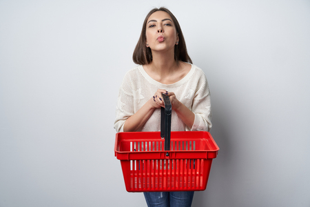 Happy woman giving empty shopping basket sending a kiss at camera. Buyer, e-commerce concept. Stock Photo