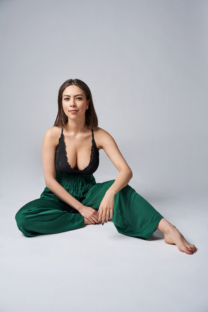 Sensual brunette female in green trousers and top with deep cleavage posing sitting on studio floor, looking at camera 免版税图像