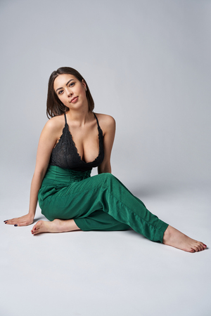 Sensual brunette female in green trousers and top with deep cleavage posing sitting on studio floor, looking at camera Standard-Bild