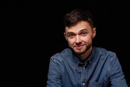 Surprised man in denim shirt looking at camera with raised eyebrows over black background