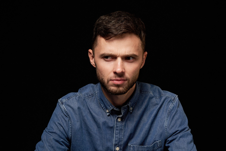 Handsome man in denim shirt looking sideways with doubtful and sceptical expression frowning over black background Фото со стока