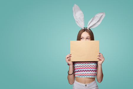 Easter mail. Girl wearing bunny ears holding a blank letter envelope peeking looking to side at blank copy space, over teal background 版權商用圖片