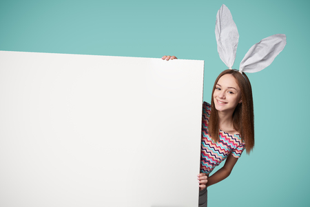 Girl wearing bunny ears holding a banner peeking, over teal background