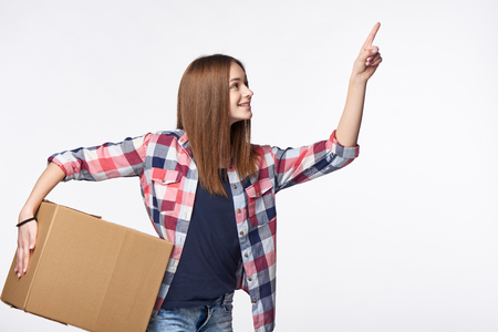 Delivery, relocation and unpacking. Smiling young woman holding cardboard box and pointing finger up or pushing imaginary button