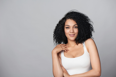 Relaxed mixed race african american - caucasian woman standing in studio over grey background looking at camera
