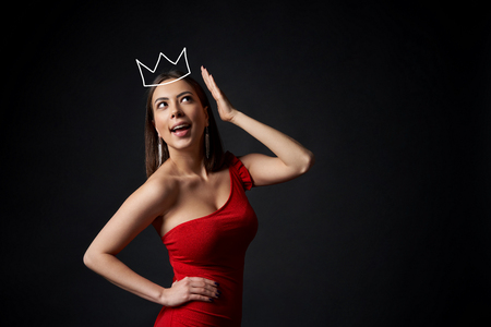 Surprised happy woman in red dress supporting her crown over dark background looking up at blank copy space