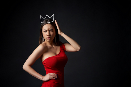 Frowning severe woman in red dress supporting her crown over dark background 版權商用圖片