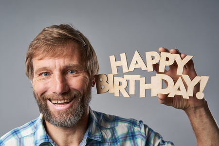 Closeup of happy mature man in checkered shirt holding happy birthday text, over grey studio background 免版税图像