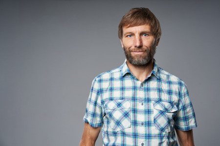 Portrait of mature man in checkered shirt looking at camera, over grey studio background