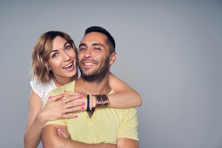 Happy couple, girl in love embracing boyfriend, looking at camera happy over grey background