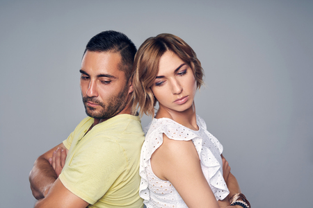 Young couple standing back to back after quarrel trying to look each at other, over grey background