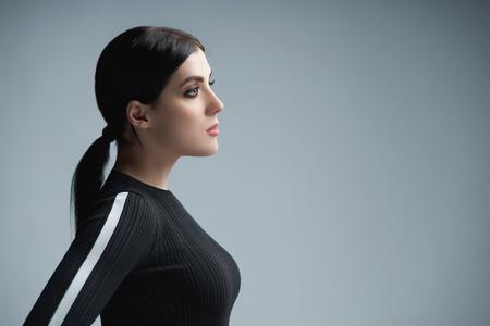 Nahaufnahmeprofilporträt der selbstbewussten Frau, die sich auf leeren Kopienraum freut, über grauem Hintergrund Standard-Bild