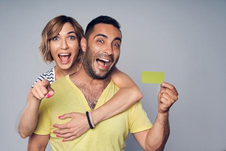 Feliz pareja sorprendida abrazada, mirando a la cámara mostrando la tarjeta de crédito en blanco y apuntando a usted, sobre fondo gris