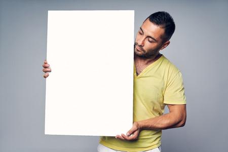 Mężczyzna trzymający pustą białą tablicę z miejscem na tekst, patrzący na tablicę, na szarym tle