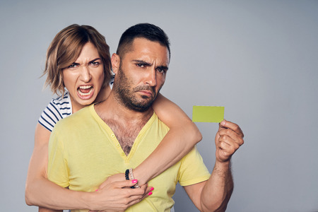 Discontent angry frowning couple looking at camera showing blank credit card, over grey background