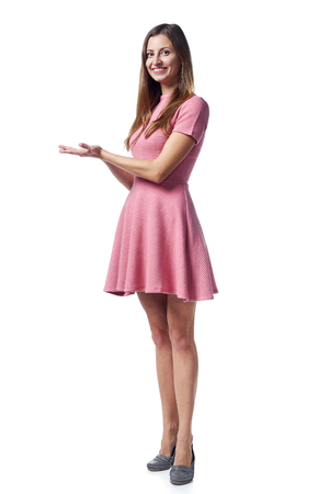 Full length of young woman in pink dress showing holding on the palm blank copy space over white background