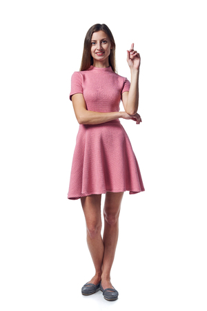 Full length of young woman in pink dress standing over white background pointing up at blank copy space looking at camera smiling