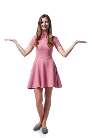 Full length of young woman in pink dress with two opened hand palms with blank copy spaces looking at camera, isolated on white background