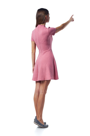 Full length of young woman in pink dress standing over white background pointing to the side at blank copy space, back view