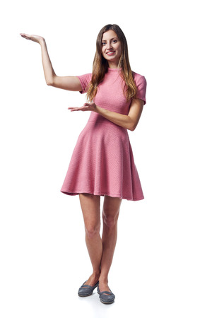 Full length of young woman in pink dress showing blank copy space over white background 版權商用圖片