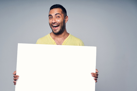 Happy laughing hispanic man holding blank white board, over gray background Imagens