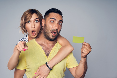 Surprised astonished couple embracing, looking at camera showing blank credit card and pointing at you, over grey background