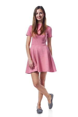 Full length of young woman in pink dress stadnign casually over white background