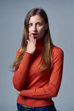 Scared impressed woman with mouth opened covering mouth by palm, over grey background