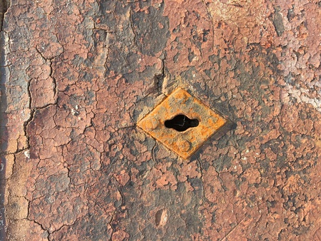 Very old weathered chappy door with rusty keyhole