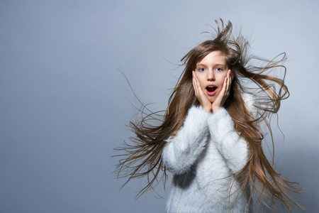 Teen girl with long hair flying in air screaming of surprise, over studio grey background Фото со стока