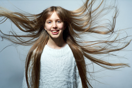 Teen girl with long hair flying in air, over studio grey background