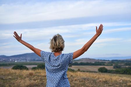 Mujer feliz disfrutando con los brazos extendidos al aire libre, vista posterior