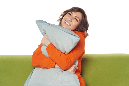 Happy young woman in home clothes sitting on sofa hugging pillow