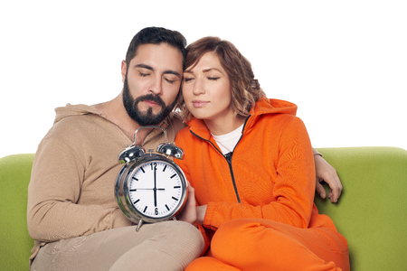 Tired sleepy young couple in home clothes sitting on sofa holding big alarm clock