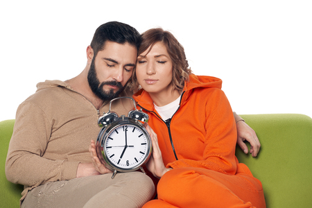 Tired sleepy young couple in home clothes sitting on sofa with closed eyes, with big alarm clock on knees Imagens