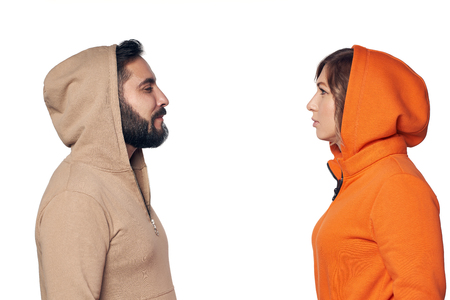 Young couple in casual clothes standing face to face looking at each other with intense
