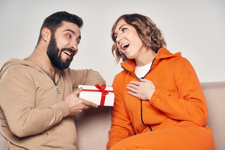 Holiday, celebration and family . Smiling man surprising his girlfriend with present at home sitting on sofa