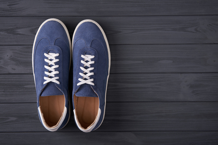 Top view of casual blue suede trainers on grey wooden planks with copy space