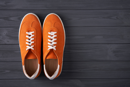 Top view of casual orange suede trainers on grey wooden planks with copy space