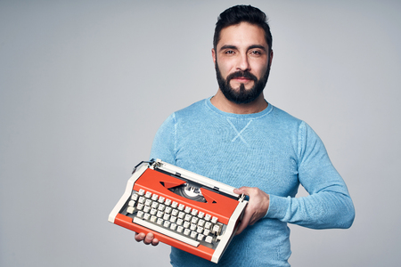 Young man in blue pullover standing holding retro typewriter, looking at camera