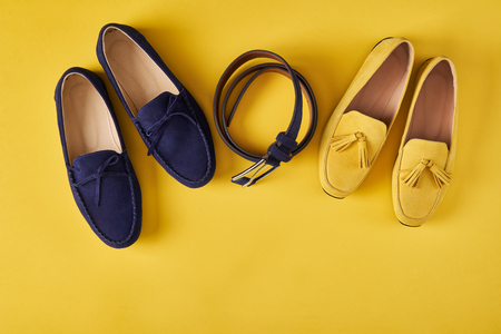Dark blue suede mans and yellow womans moccasins shoes with a belt over yellow background, top view