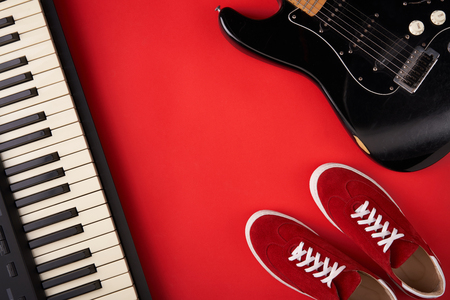 Music band concept. Electric guitar, synthesiser and red stylish sneakers, on red background, flat lay photography Stock Photo
