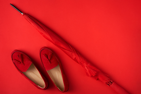Bright red shoes and umbrella on red background, top view style. Bright autumn concept