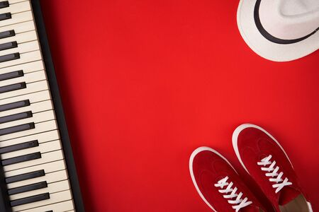 Music band concept. Electric guitar, synthesiser and red stylish sneakers, on red background, flat lay photography