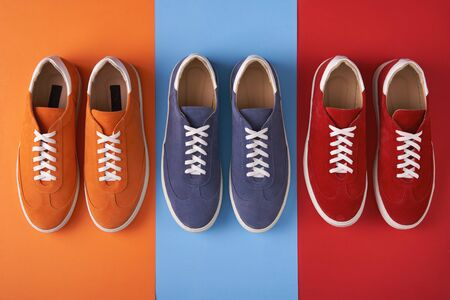 Three pairs of colorful casual unisex suede sneakers standing in line on multicoloured background, flat lay style